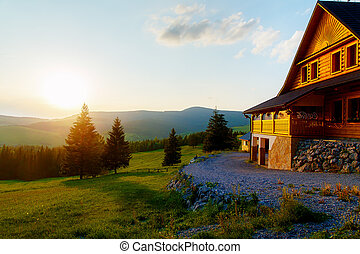 Rural cottage in the mountains and green meadow. Sunset...