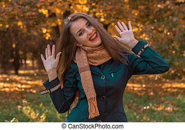cheerful young girl with long hair in the Park and rage lifted her hands up