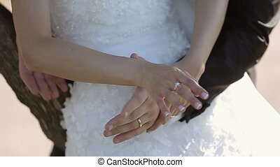 Wedding couple embracing by hands closeup