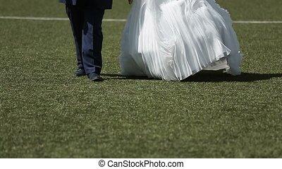 Wedding couple walking on soccer field slowmotion