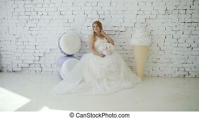 Cute young blonde woman in wedding dress with flowers...