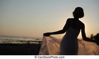 Bride walking on a evening beach slowmotion