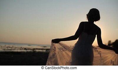 Bride walking on a evening beach