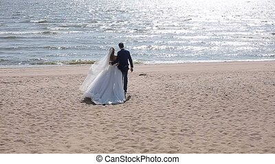 Bride and groom walking on a beach back