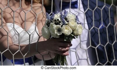 Bride and groom near soccer gate unrecognizable