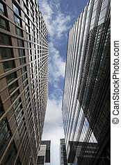 Low angle view of skyscrapers in front of blue sky. Business...