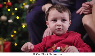 Baby closeup. A child in a red sweater with a fawn stares at...