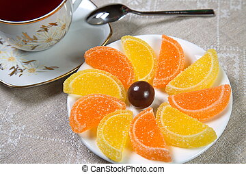 Marmalade on a saucer and a cup of tea. One candy.