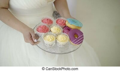 Young woman in wedding dress takes plate with candies shot