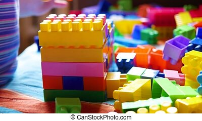 A young child plays in the constructor. Game of the children's designer. Colored cubes.