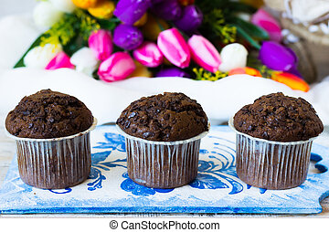 Three chocolate muffins on a background of tulips -...