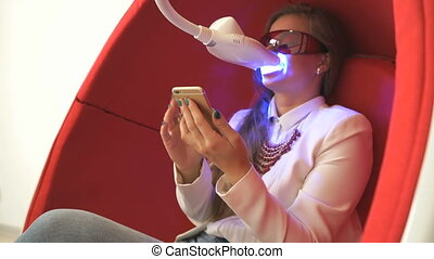 Woman client sitting in chair during whitening - Young woman...