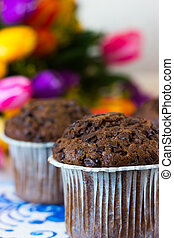 Chocolate muffins on the background of tulips - Chocolate...