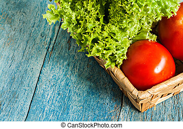 Fresh green salad lola rossa and tomatoes on blue wooden...