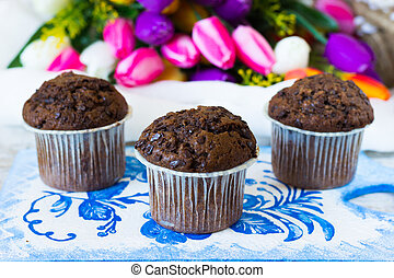 Three chocolate muffins on a flowers background - Chocolate...