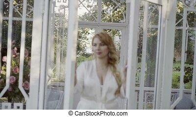 Cute young blonde woman in lingerie open glass doors defocus...