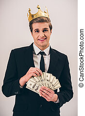 Handsome rich guy - Handsome young man in suit and crown is...