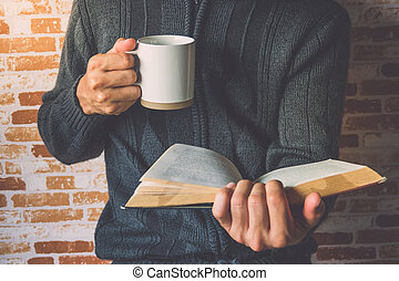 A man holding a cup of coffee and reading book on relaxing...