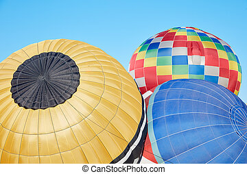 Colorful hot air balloons inflating on ground, blue sky