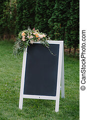 Chulk board, which stands on the grass with wedding...