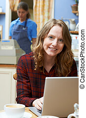 Woman In Coffee Shop Using Laptop Computer