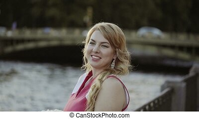 Cute young blonde woman in red dress staying on embankment...