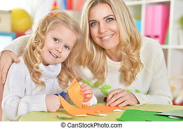 mother with little daughter cutting figures from paper