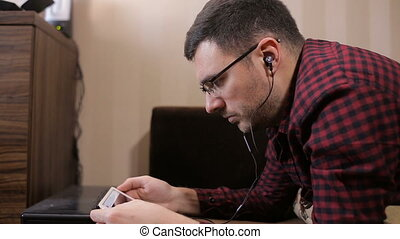 Caucasian man using digital tablet on sofa and listening to music