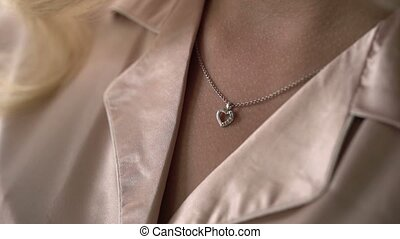 Woman touching pendant on her neck shot