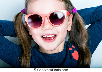 Cheerful smiling cute child with teeth dropped out - preschooler girl in sunglasses with open mouth without milk tooth
