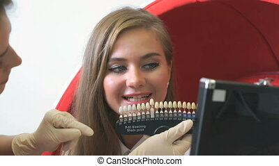 Young woman client looking at teeth tones variety