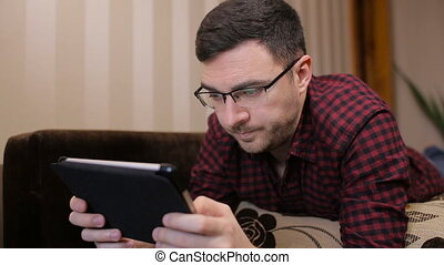 Technology, vision and people concept - man with tablet pc tired from eyeglasses at home