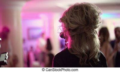 Unrecognizable woman singer on concert shot