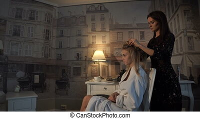 Hairdresser makes hairstyle girl at home, preparing her for...