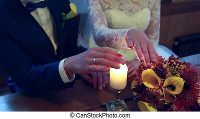 On a wedding day groom puts a wedding ring on finger of a bride. Bride puts a ring on finger of a groom