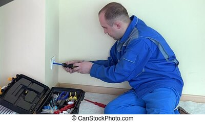 Angry electrician man with indicator test voltage on electric wall socket