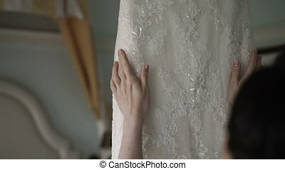 Bride touching wedding dress shot