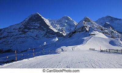 Ski slope and snow covered mountaind Eiger, Monch,...