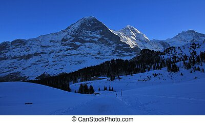 Eiger north face in winter. Famous mountains Eiger, Monch...