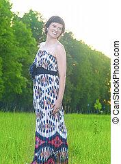 Full Length Portrait of Smiling Caucasian Brunette Woman Posing Outdoors at Sunset.