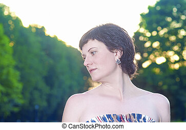 Portrait of Smiling Caucasian Brunette Woman Posing Outdoors at Sunset.