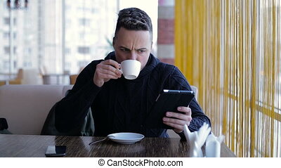 Young man with tablet computer drinking coffee in cafe