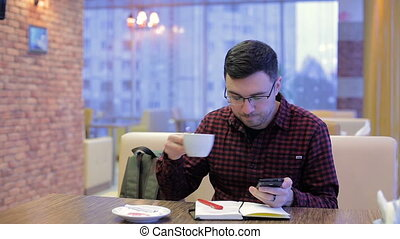 Adult man talking on phone and writing in a notebook in cafe