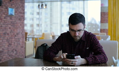 Young man texting on smartphone in cafe - Handsome young man...