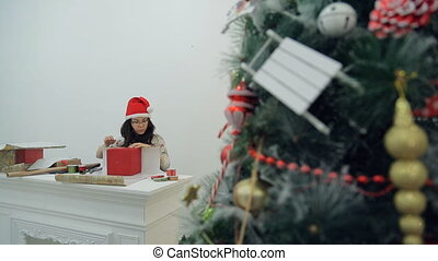 Asian Brunette sitting at the table for Christmas tree gifts packs.