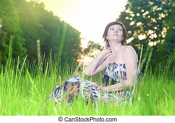 Portrait of Relaxing Caucasian Brunette Woman Posing Outdoors on Nature Background at Sunset.