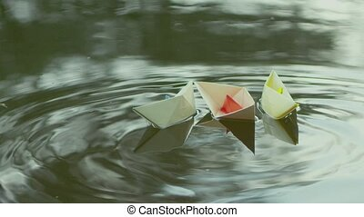 Beige paper boat floating on a green river. - Three paper...