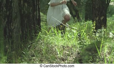the girl runs into the forest on the grass