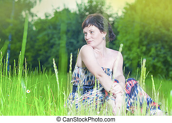 Portrait of Happy Smiling Caucasian Brunette Woman Posing Outdoors on Nature Background at Sunset.