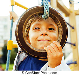 little cute boy hanging on gymnastic ring at playground...